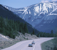 Two cars traveling on an Alaska highway.