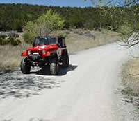 Off road vehicle traveling on dirt road