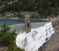Photo of a dam with water flowing over the top.